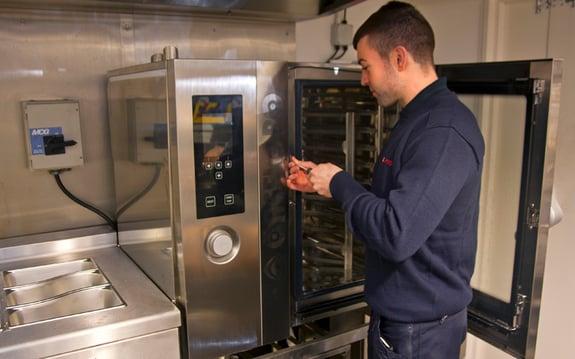 An engineer fixing a piece of kitchen equipment