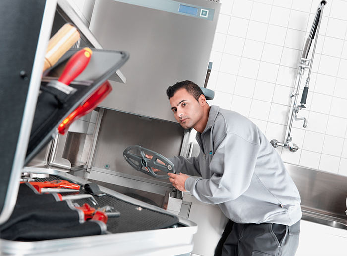 An engineer repairing kitchen equipment