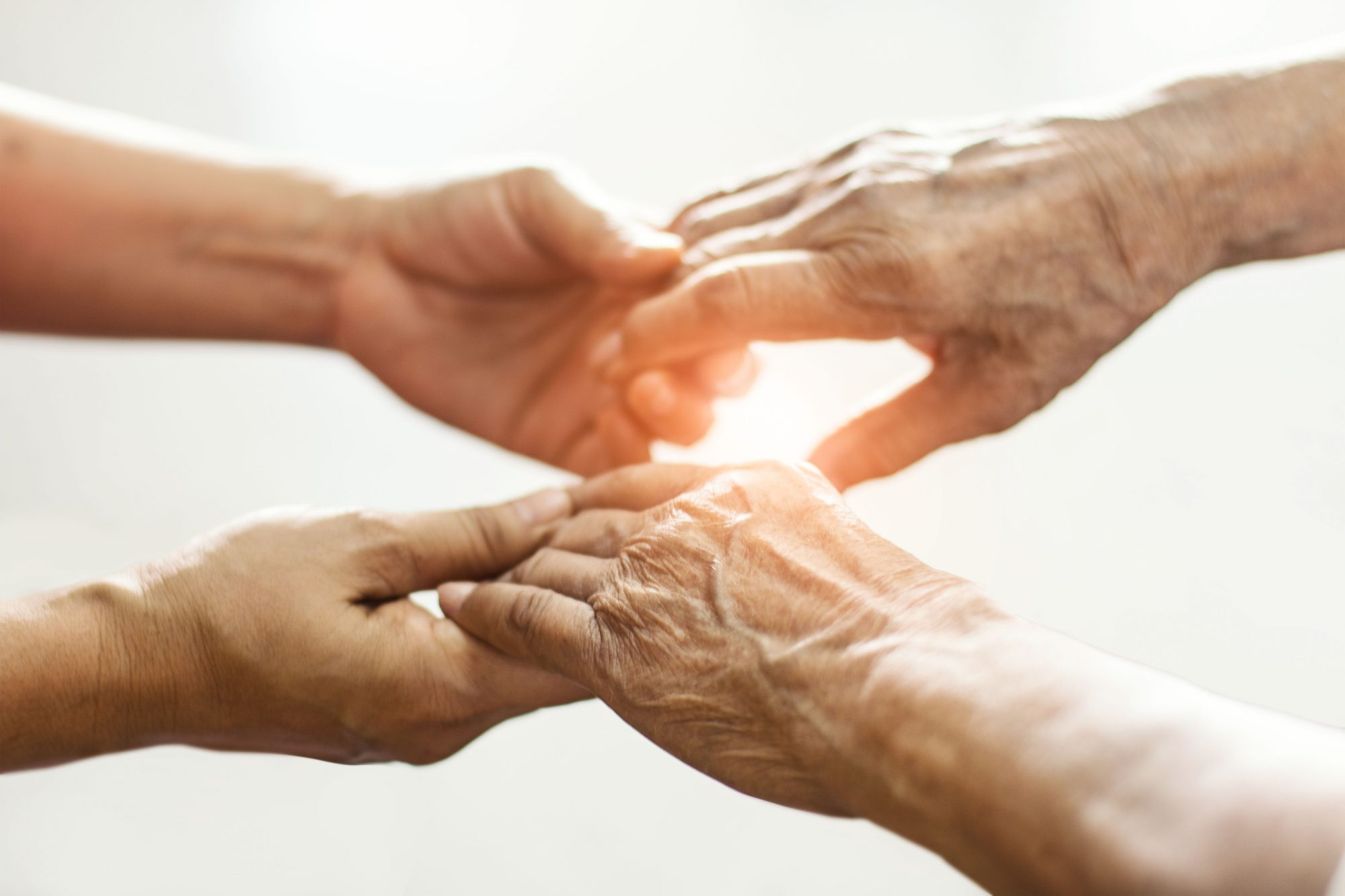 An elderly pair of hands in those of someone younger