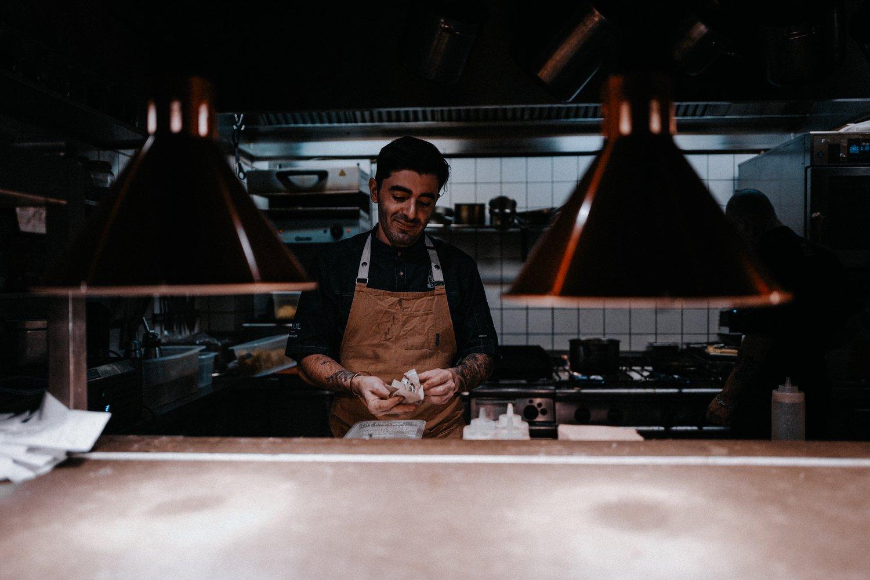 A restaurant kitchen with chef preparing food