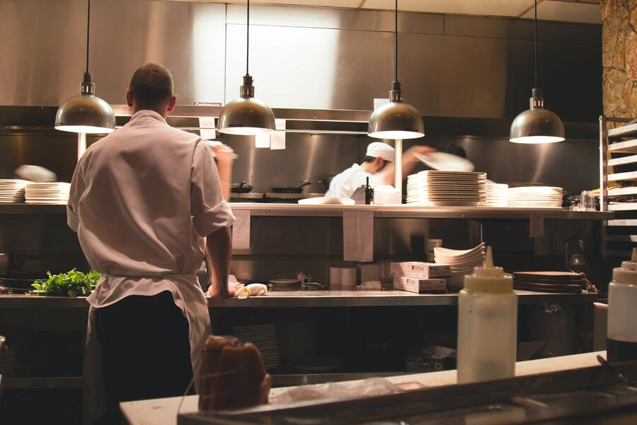 A chef waiting at the pass for dishes